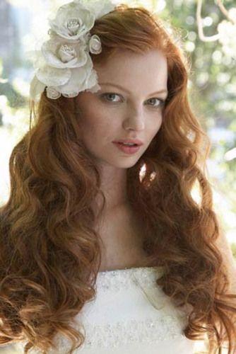 Acconciatura da sposa con capelli lunghi, scioleti e ondulati ed un fiore bianco su una tempia