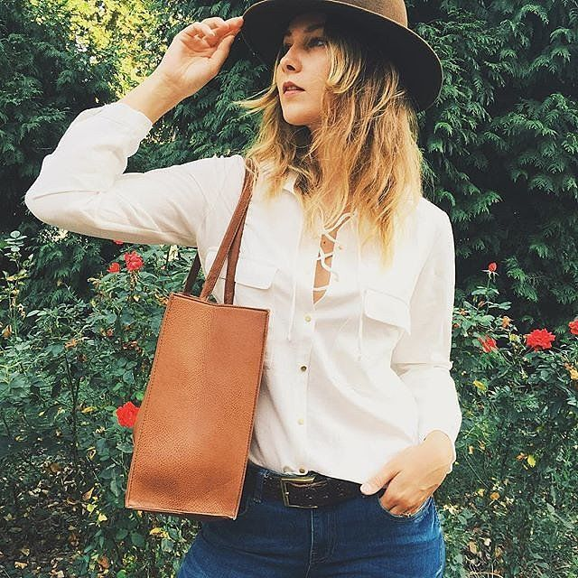 A white blouse, jeans, a felt hat, and a leather tote.