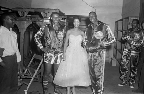 Two unidentified Harlem Globetrotter basketball players posing with unidentified woman in formal dress.