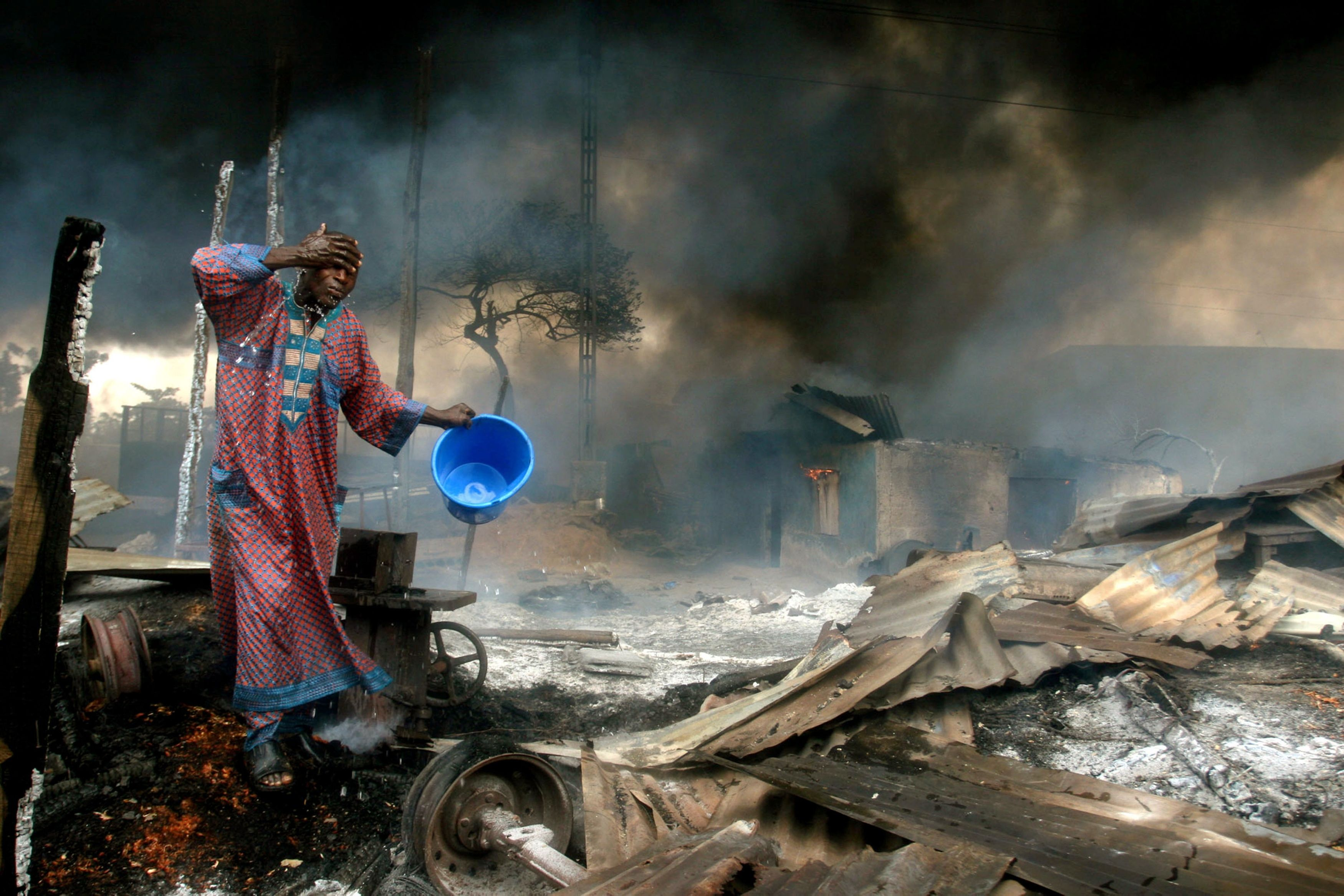 File photo of a man rinsing soot from his face at the scene of a gas pipeline explosion near Nigeria's commercial capital Lagos