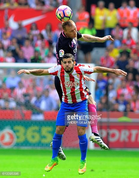 Barcelona's French defender Jeremy Mathieu vies with Sporting Gijon's forward Victor during the Spanish league football match Real Sporting de Gijon...