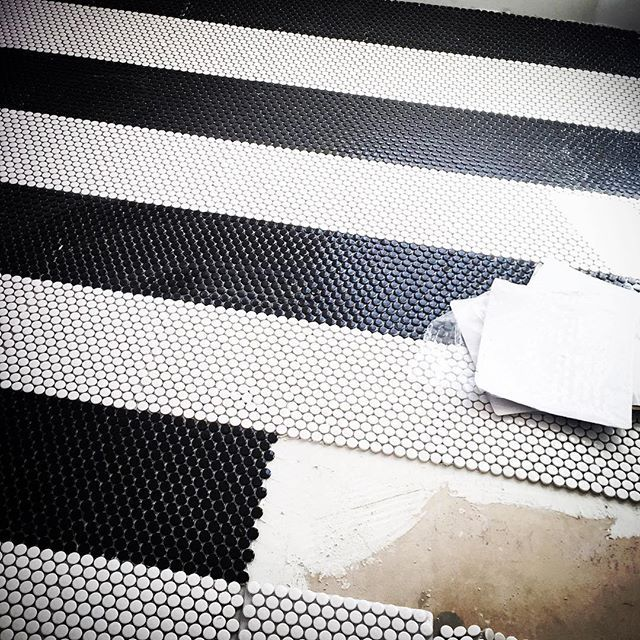 Black And White Striped Penny Tiles On A Laundry Floor F