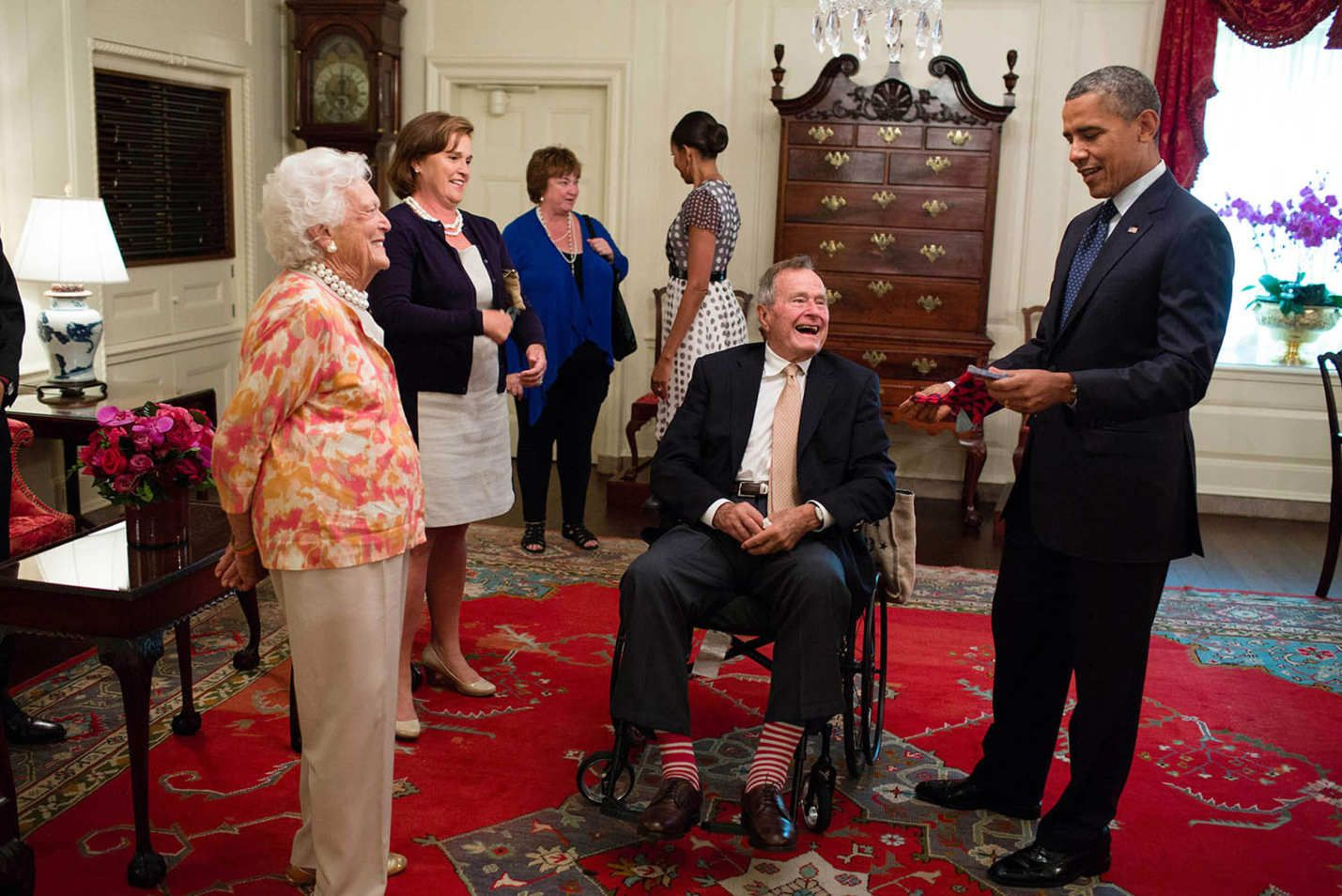 Former President George H. W. Bush and former First Lady Barbara Bush presenting the president with a pair of socks in the Map Room of the White House.