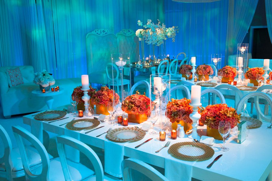 Sleek modern white reception decor with orange flowers | Photo ...