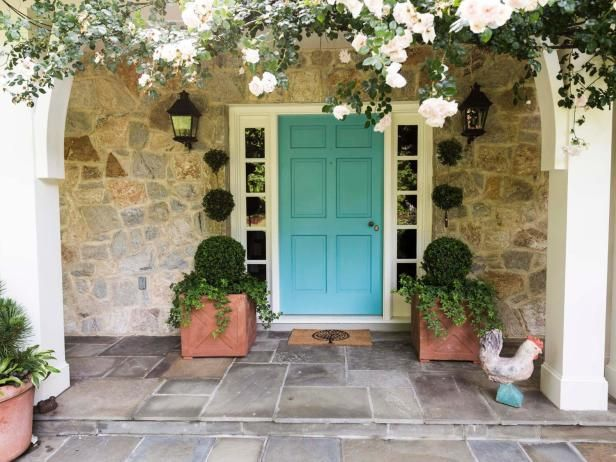 Planters Of Boxwood Topiaries Flank The Front Door With A Pink Climbing  Rose Partially Shrouding The