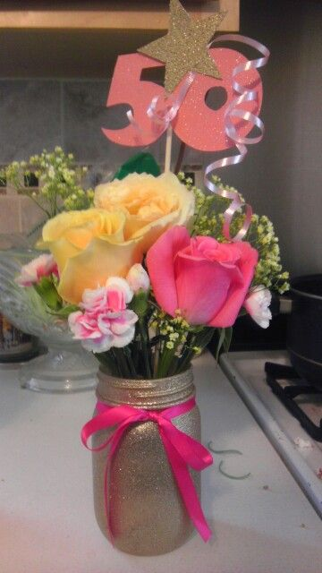 50th birthday party- pink, yellow, and gold. Spray paint mason jar with gold glitter, add ribbon.