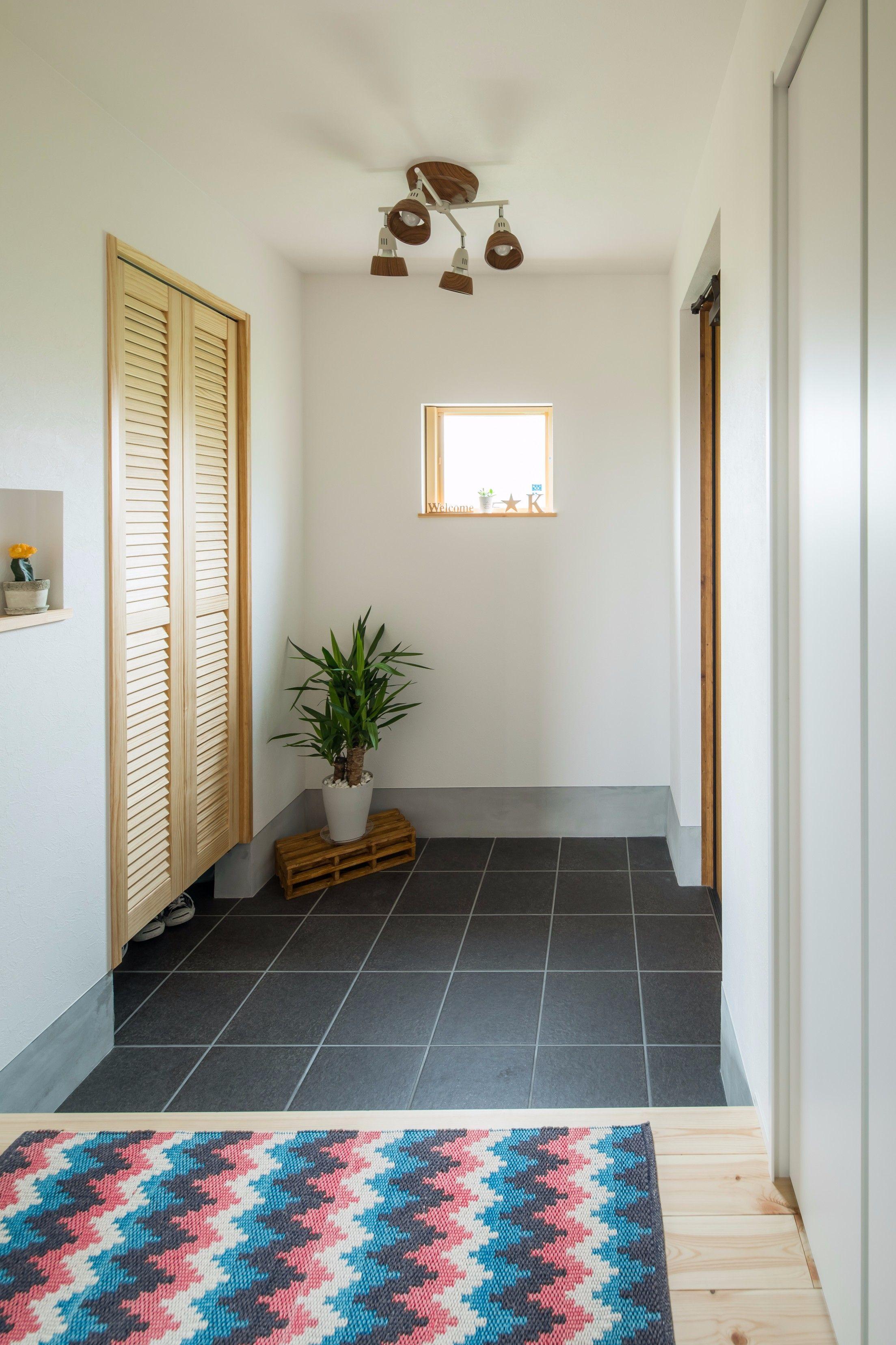 正方形の窓から光が差し込む玄関 窓 折戸 床と揃えられた淡い木の色