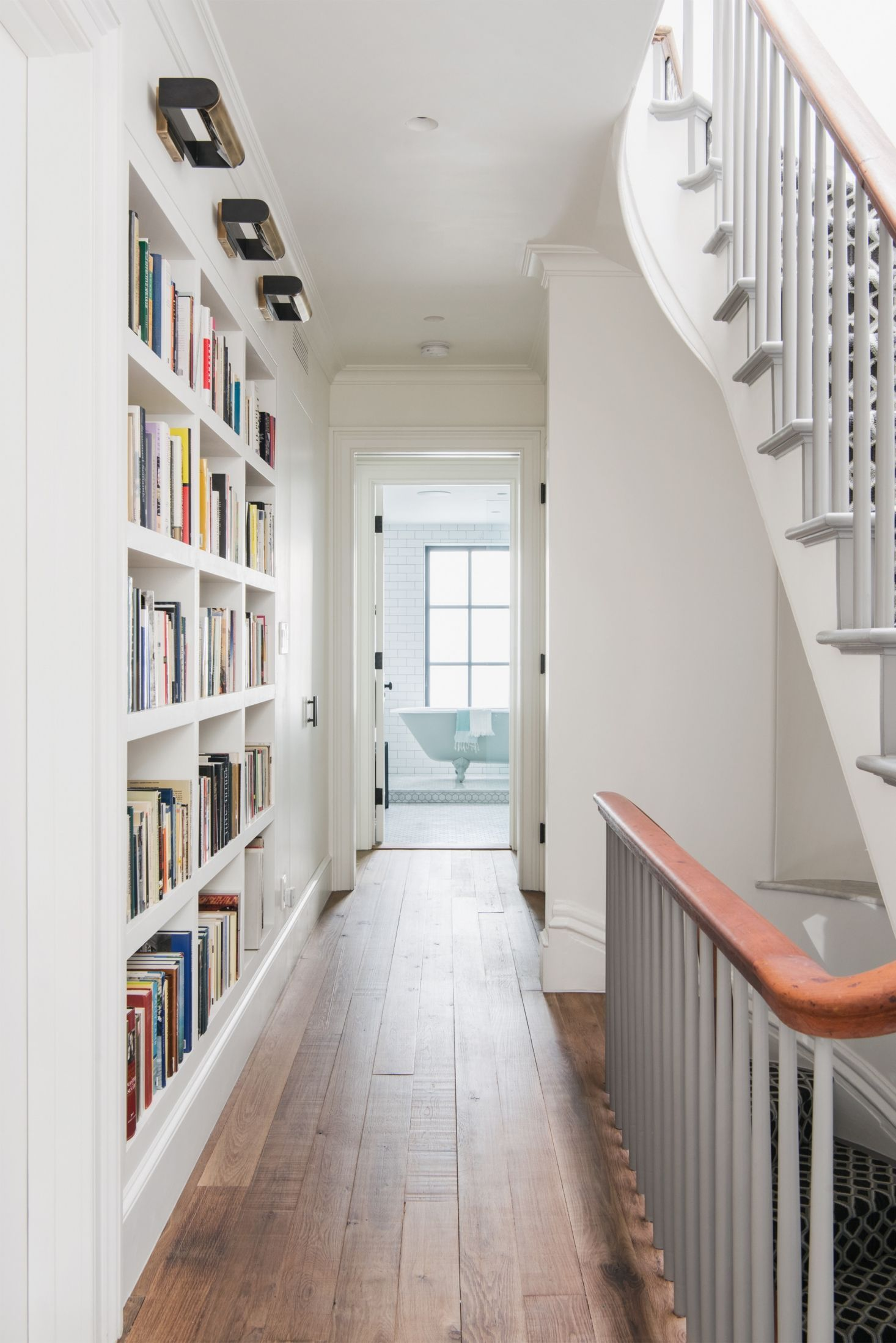 Narrow hallway decor  A builtin bookcase beautifully maximizes storage space in this