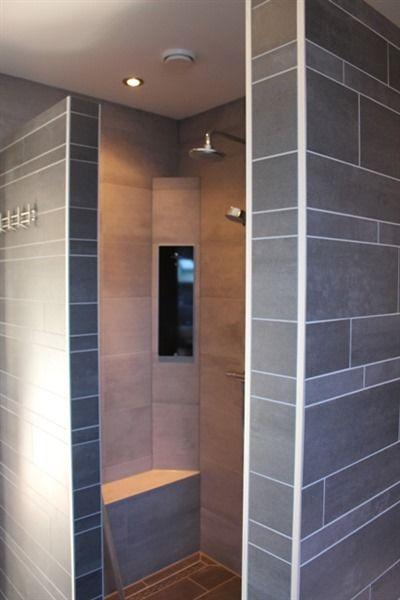 Inloop douche met muurtjes met stroken tegels. Het zwarte paneel dat ...