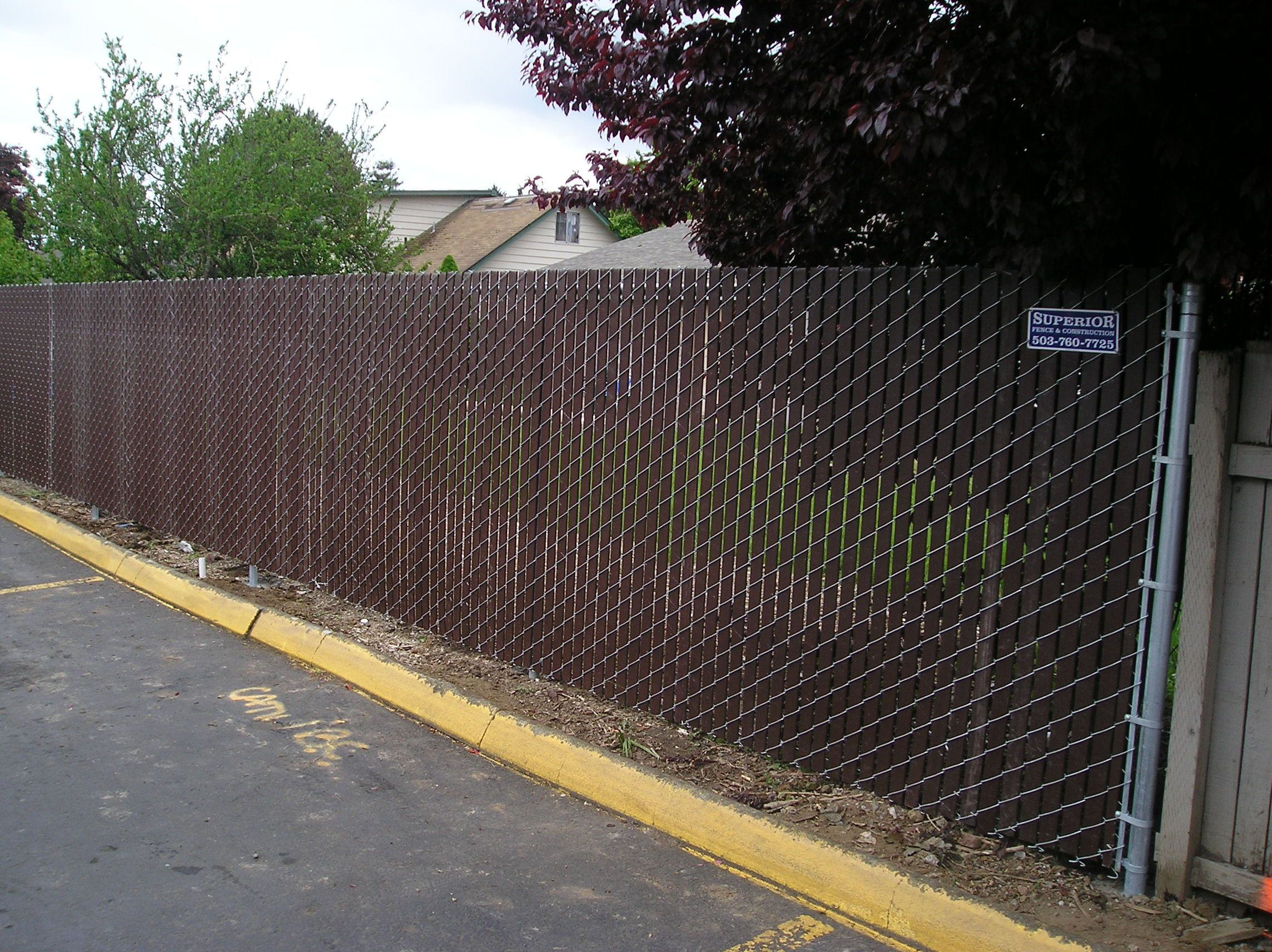 chain link fence with brown slats for privacy