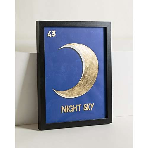 The dreamy Night Sky Gold Foiled Wall Art is celestial-inspired, featuring a vintage-style crescent moon illustration and 'Night Sky' text with opulent shiny gold foiling, offset by a navy blue background. This wall art was originally designed in the OB Studio and is framed in a black frame. Display with the matching gold-foiled Lucky Star, Sol, and Amor wall art prints for an impactful gallery-style look.