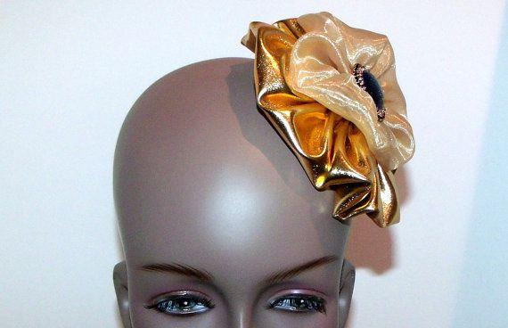 Gold lame fascinator, hat, hair  piece with a Swarovski rhinestone black opal button.. $18.98, via Etsy.