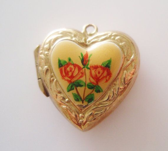 This is a beautifully detailed 9 ct gold heart locket with enamelled roses on a yellow background.  It weighs 2.4 grams, measures 1.6 cm by 1.6