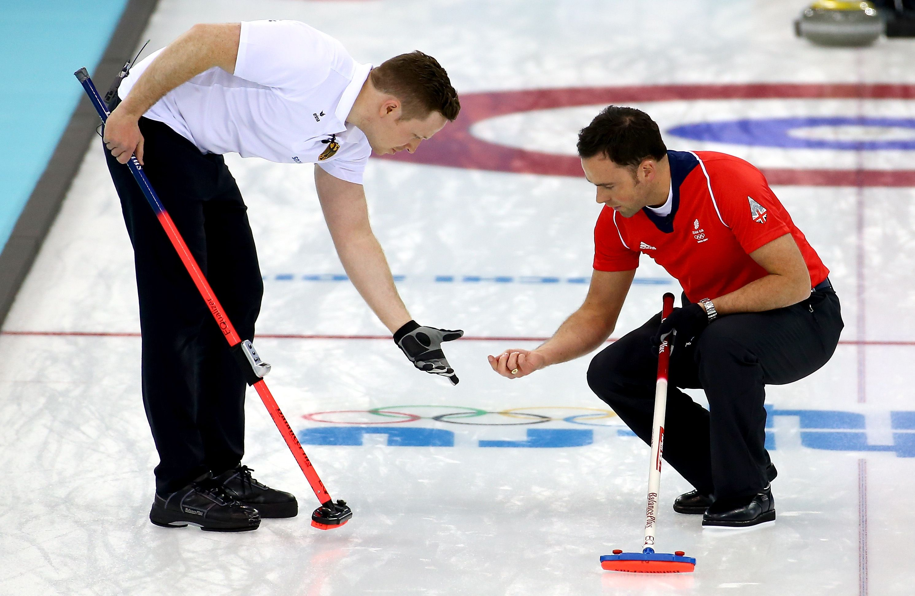 Christopher Bartsch of Germany and David Murdock of Great Britain check the ice in the men's round robin session (c) Getty Images