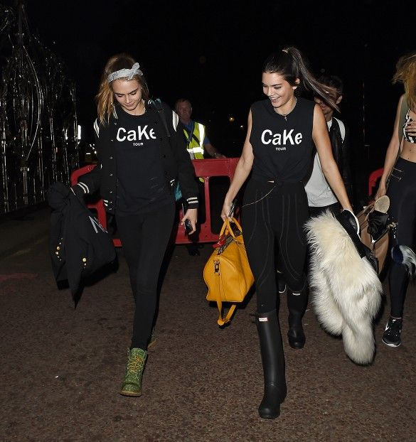 Cara Delevingne wears her customized shirt with black pants, a varsity jacket and green lace-up boots. Kendall Jenner is wearing her shirt with black pants, Hunter rain boots, and a yellow duffel.