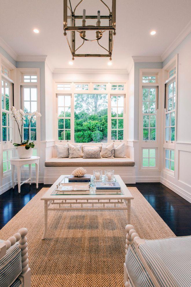 Family room, large windows, window bench, natural fiber rug, striped chairs, glass coffee table, dark wood floors | Build Prestige Homes Pty Ltd