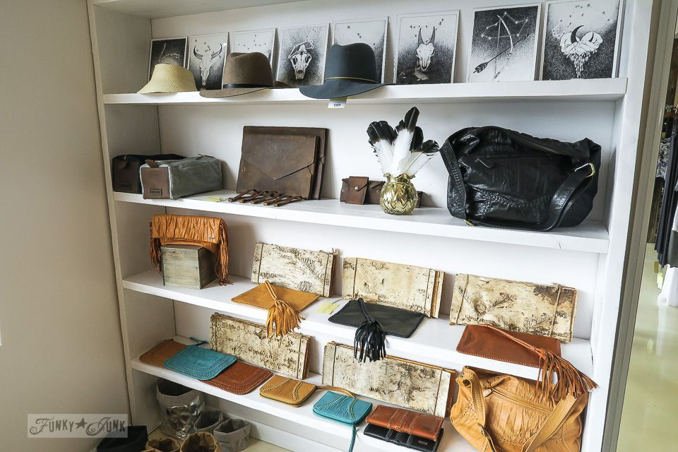 Wide bookshelf with accessories, purse, art, and clothing storage.
