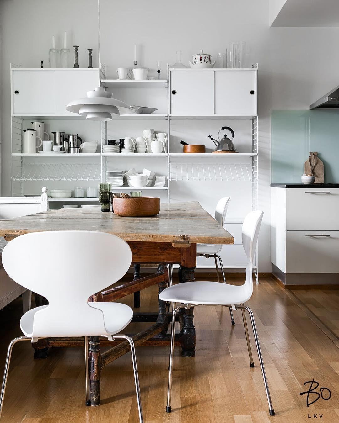 Puinen ruokapöytä tuo kodikasta kontrastia modernille valkoiselle String hyllykölle ja muille kalusteille.