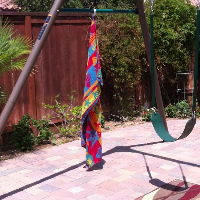 Hanging out to dry! We have a big family, so I sewed tabs with Velcro on each beach towel. Now I hang them out to dry on our swing set.