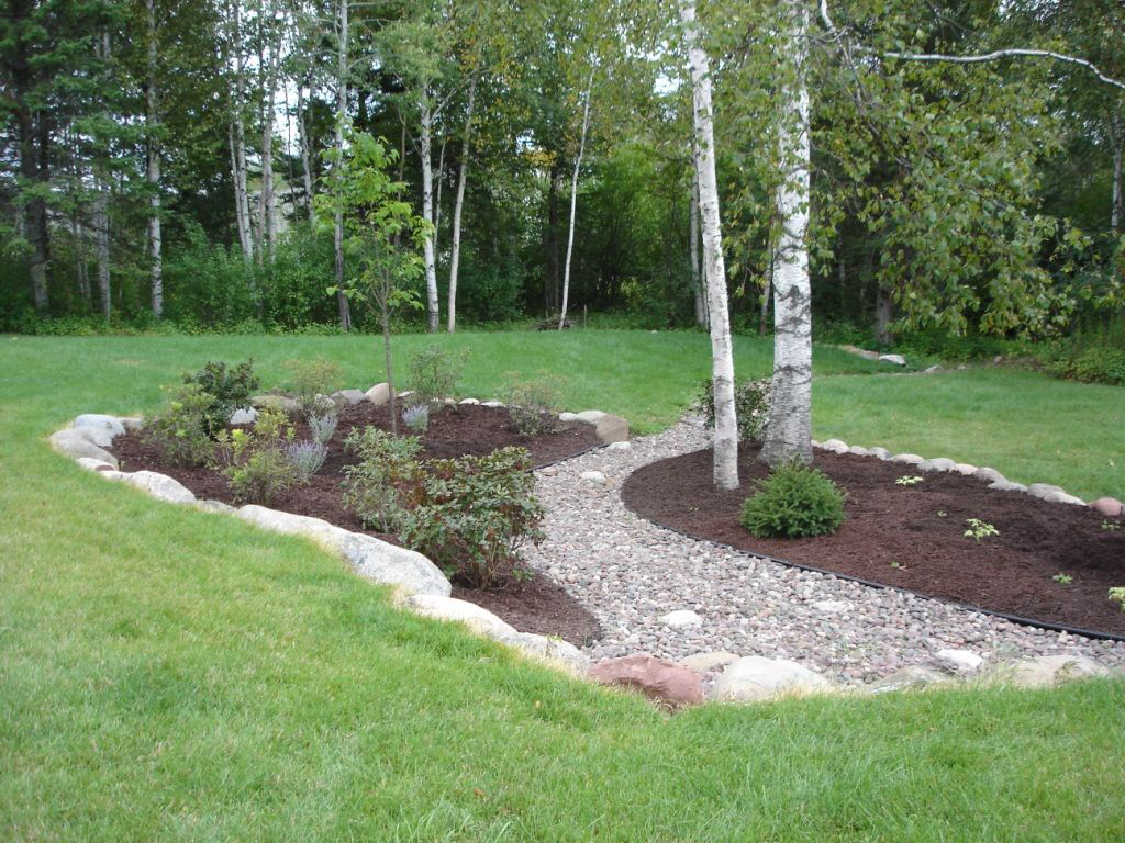 Dry Creek Bed With Landscaping Like The Rock Wall Idea For Slopes Sloped Backyar Landscaping With Rocks Sloped Backyard Landscaping Landscaping Around Trees