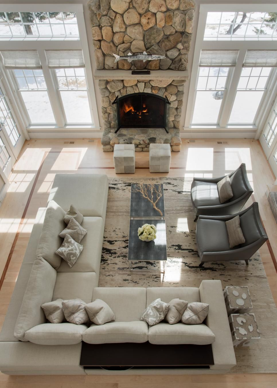 A Dramatic Floor To Ceiling Stone Fireplace Is The Focal Point In This Two Story Coastal Style Living Room Neutral Sectional And Wood Coffee Table Add