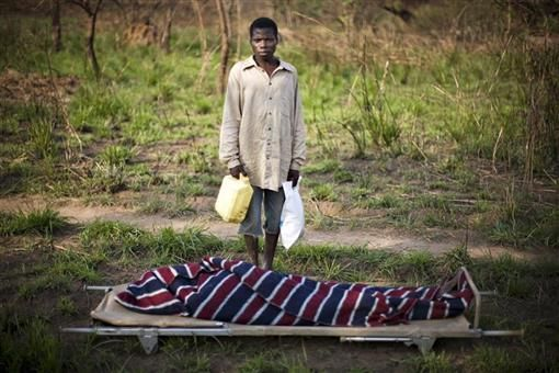 Roger Mbuliundo stands beside the body of his father Dieudonne Kulimbo, 60, who was shot and killed in the bush near Dungu in northeastern Congo, February 17, 2009.  REUTERS/Finbarr O'Reilly