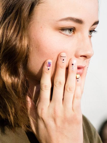 """""""Good, minimalist nail art isn't always easy to find on the runways, but this clear base topped with graphic shapes is pretty much perfect. The one black-and-iridescent accent nail is beautiful, and the subtle cuticle art makes it a little more interesting."""" —Stephanie Saltzman, associate digital editor"""