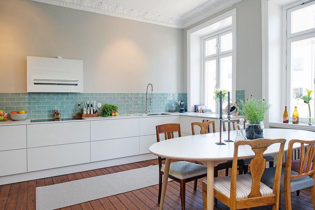 Cocina blanca con azulejos en tono agua con un comedor rstico con