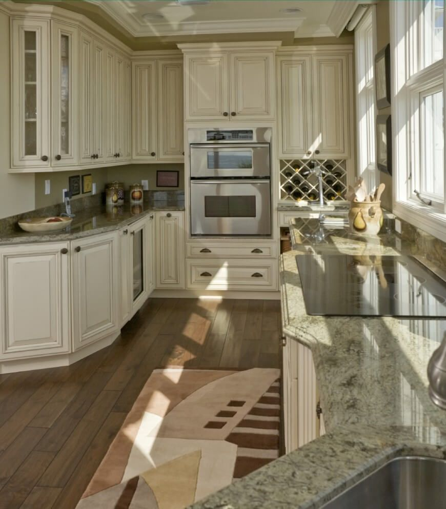 This Kitchen Makes The Most Of Its Narrow Presence With Bold And Detailed  White Cabinetry Over Dark Hardwood Flooring, Plus Light Green Granite  Countertops ...