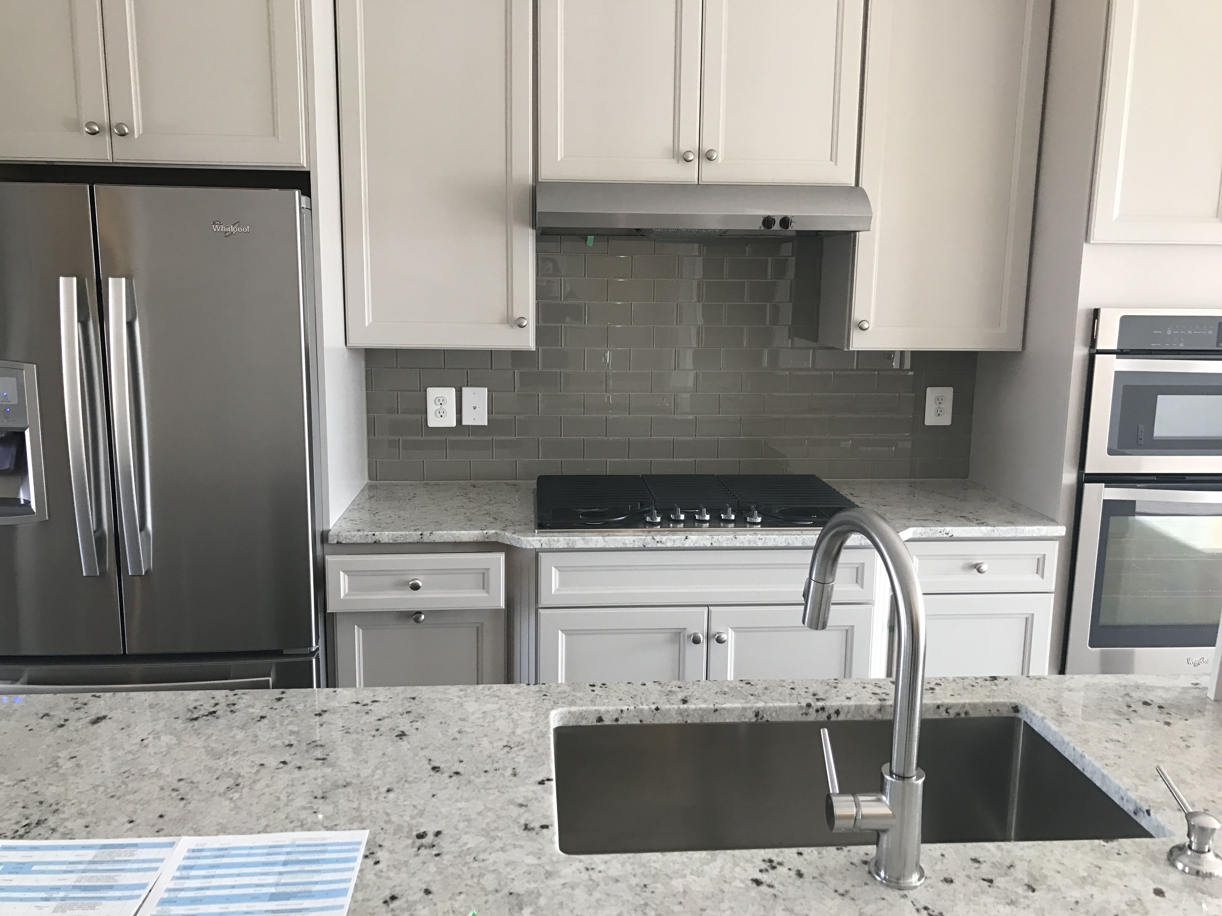 Grey Kitchen Cabinets With Glass Subway Tile Backsplash And Bianco