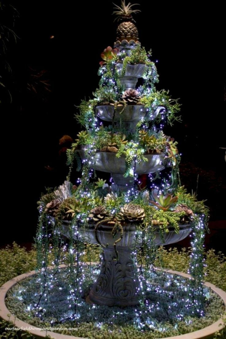 A stunning succulent fountain draped in fairy lights at