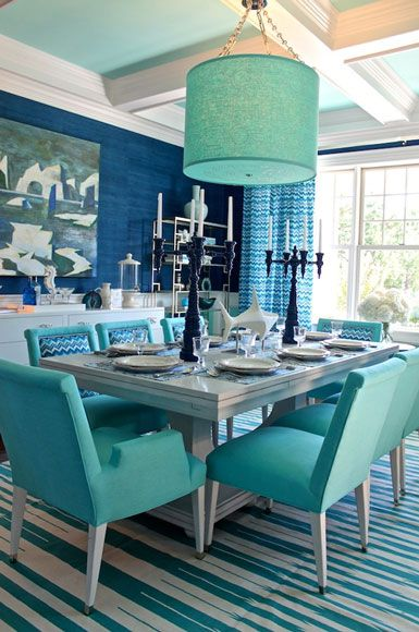 Turquoise dining room set, composed by a modern white dining table for 8, turquoise dinning chairs, turquoise suspension lamp. A colour theme project by Interior Designer Kelly Wearstler