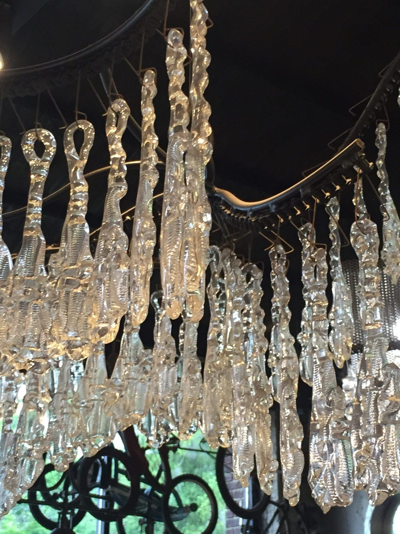 A chandelier made out of blown glass crystal and old motorcycle a chandelier made out of blown glass crystal and old motorcycle chains hangs in the arubaitofo Choice Image