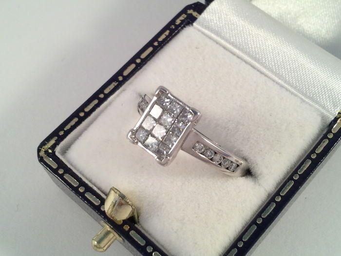 18 karaat wit gouden ring met princes en briljant geslepen diamanten 104 ct - ringmaat 17/54  Deze schitterende 18 karaat wit gouden ring is op bijzondere wijze gesmeed en gezet met 12 princess geslepen diamanten. De bovenkant van de ring is gesmeed in een rechthoek in een strak eigentijds design. Op de schouders zijn aan beide kanten 5 briljant geslepen diamanten gezet.Totaal 104 ct. Een prachtig bezit. De bovenkant van de ring is 1 cm bij 7 mm.Diamant12 x 007 ct princess geslepen G-H /VS…