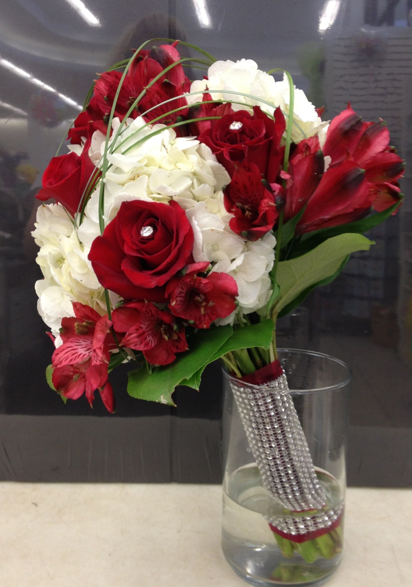Red, White and Bling Bride Bq.  White hydrangea, red roses and red alstroemeria with bear grass loops and salal leaves around base wrapped in red satin and bling.