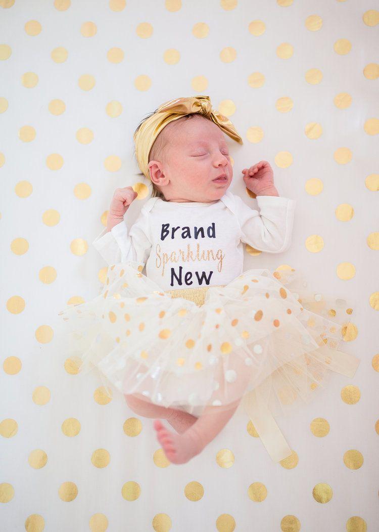 Lifestyle newborn photography brand sparkling new baby onesie newborn pictures taken at home