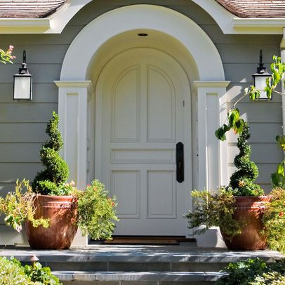 This classy arched entrance and door can stand alone without the planters.