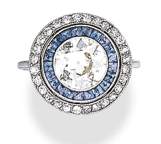 A DIAMOND AND SAPPHIRE RING Bezel-set with an old European-cut diamond, within a French-cut sapphire and old European-cut diamond surround, mounted in 18k white gold, with French assay marks