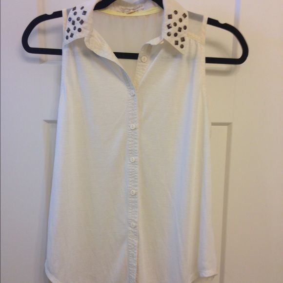 Cream sleeveless button up Cream sleeveless button up.  Studs on the collar and the back is sheer. Rewind  Tops Button Down Shirts
