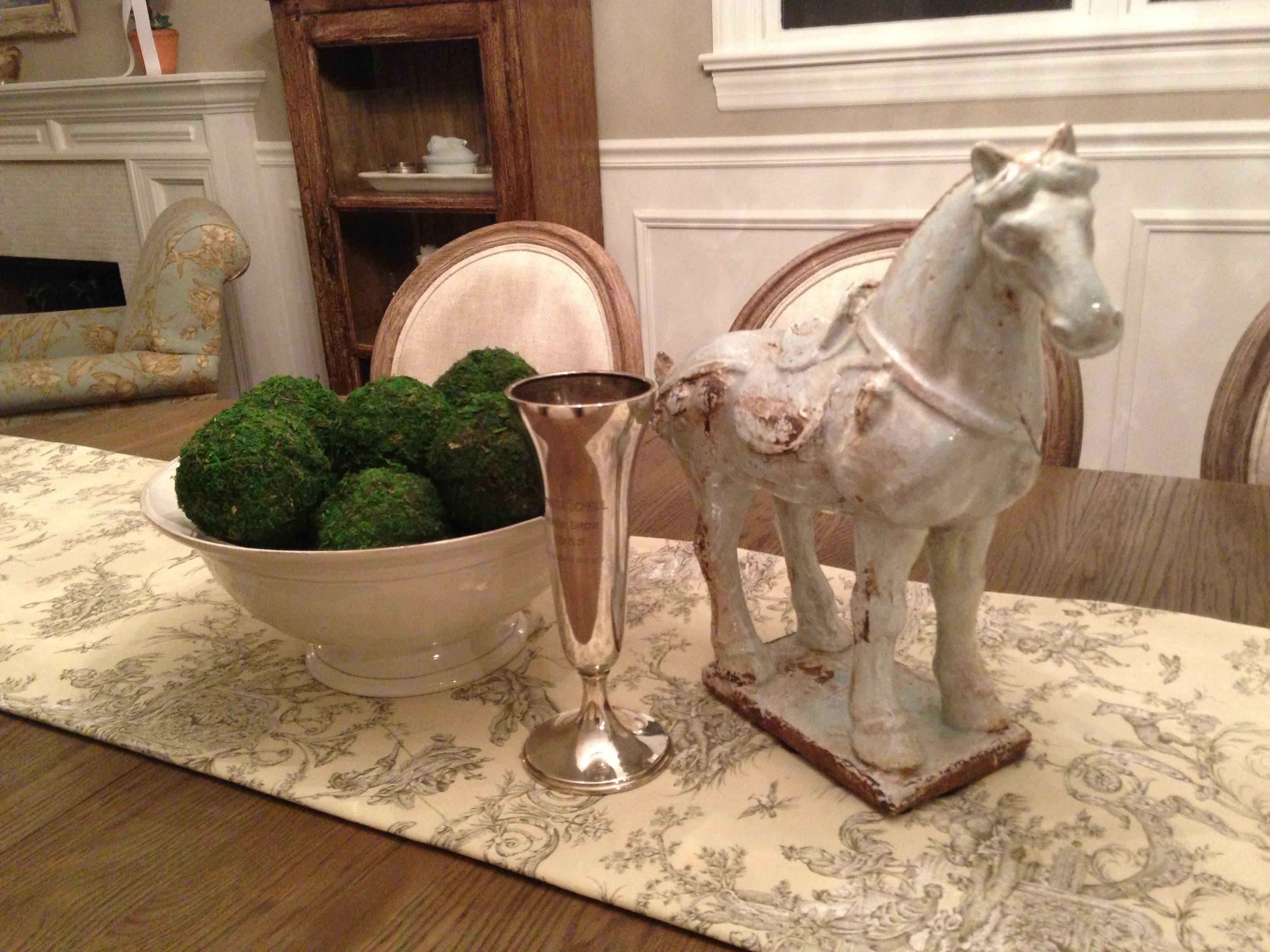 The homeowner displays a cherished trophy cup from her grandfather's equestrian days, reimagined as part of the centerpiece vignette. What a beautiful and meaningful tribute! Handmade moss balls are gathered in a rustic cream pottery bowl, while a ceramic steed stands guard.  www.ShamrockHillDesigns.com (photo credit: Anne Brinsmade)