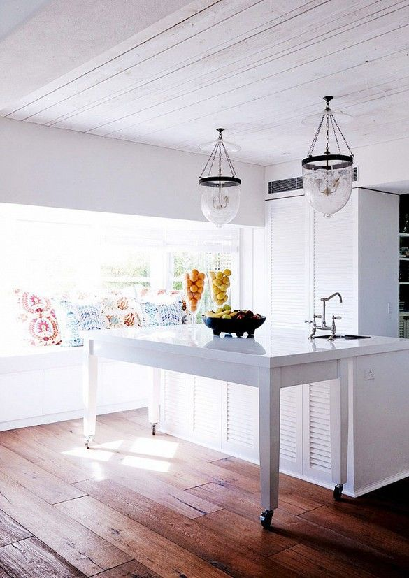 White kitchen with marble island and love seat/bench in window // two glass chandeliers and fruit displays