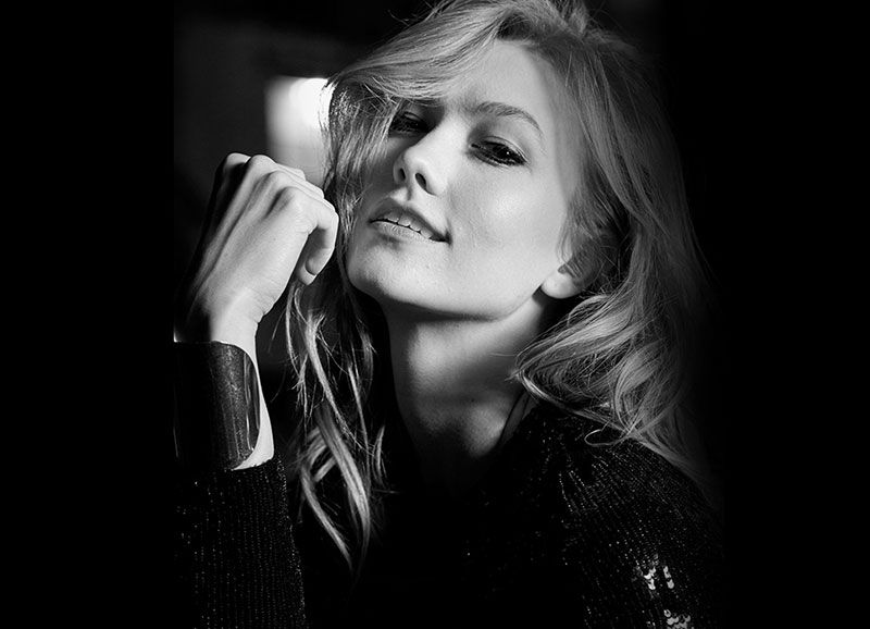 Photographed in black and white, Karlie Kloss gives a coy look on set of Carolina Herrera fragrance shoot