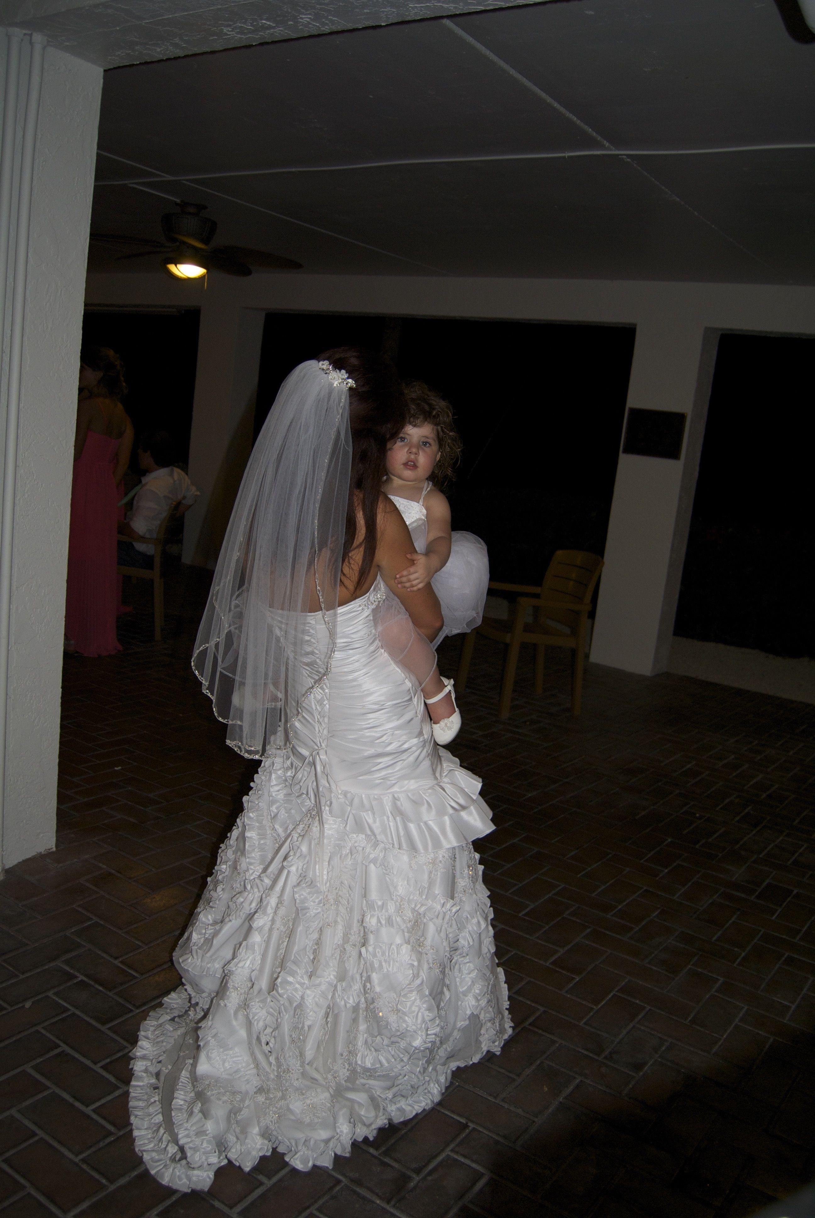 Bride holding the adorable flower girl