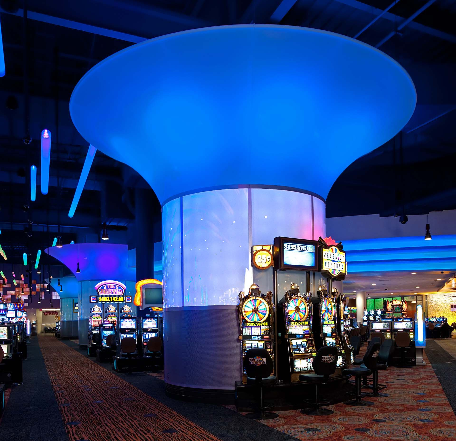 Firekeepers Casino | Columns // the high columns utilize a combination of four different materials: acrylic, aluminum, 16 gauge perforated steel panels, and a 24 ft diam. translucent fabric cone top // Hospitality Engineered Fabricated Vibrant Lighting