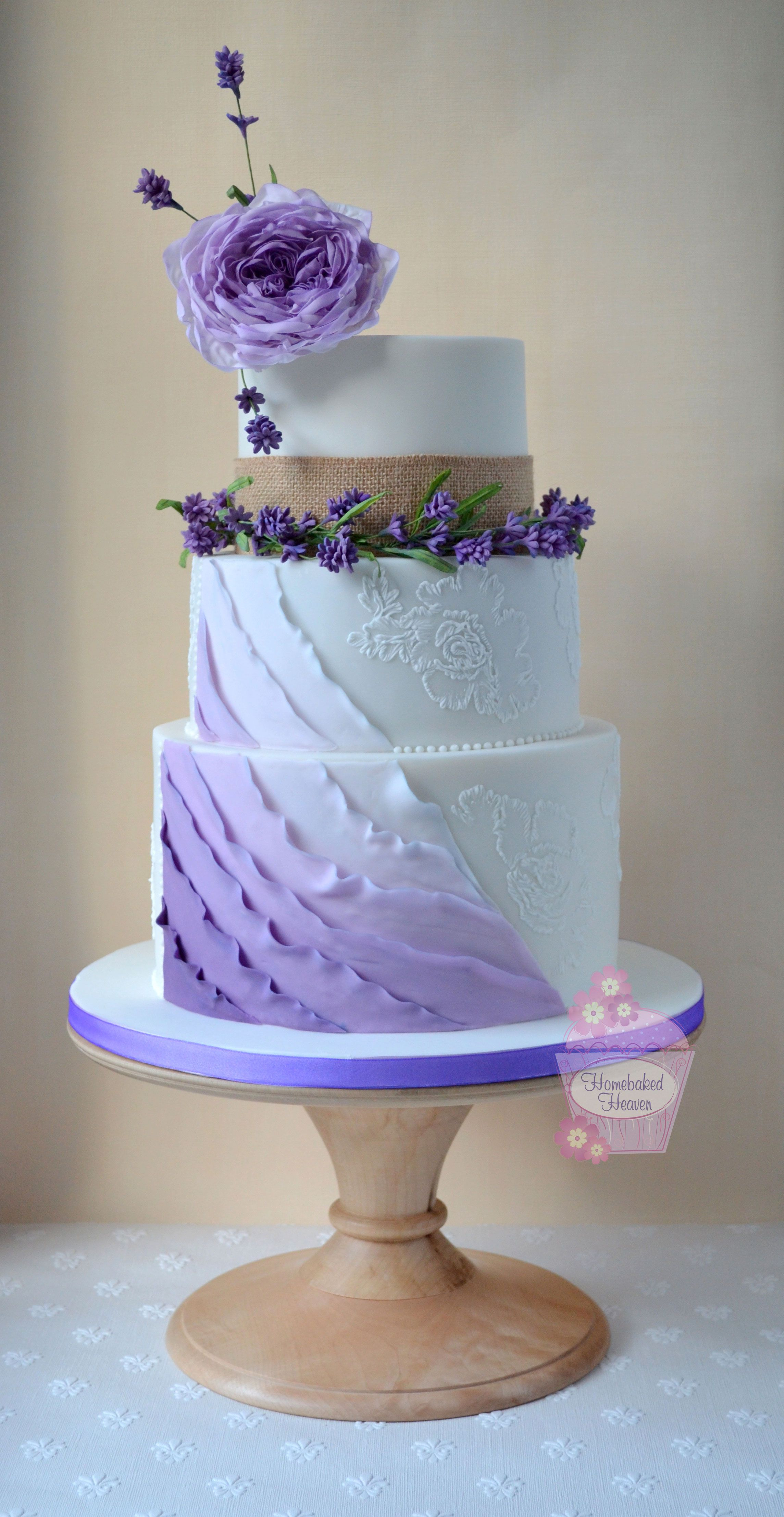 Wedding cake with ombre ruffles sugar lavender garland topped with