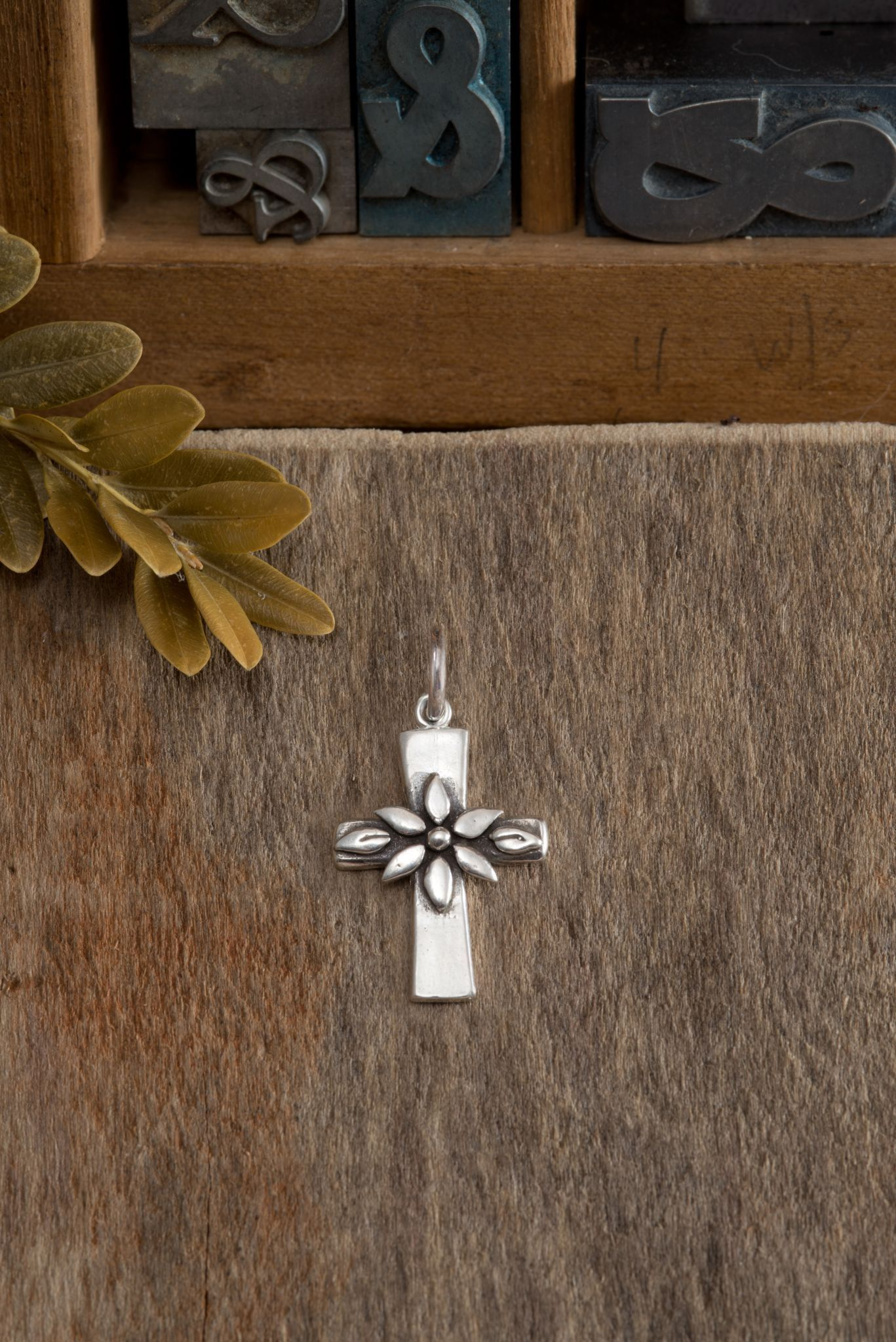 """Sterling silver cross adorned with blooming flower represents new life in Christ. Pendant measures approximately 1""""x 5/8"""" All sterling silver..."""
