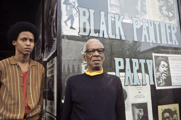Black Panther Party members stand in front of flyers of imprisoned party members