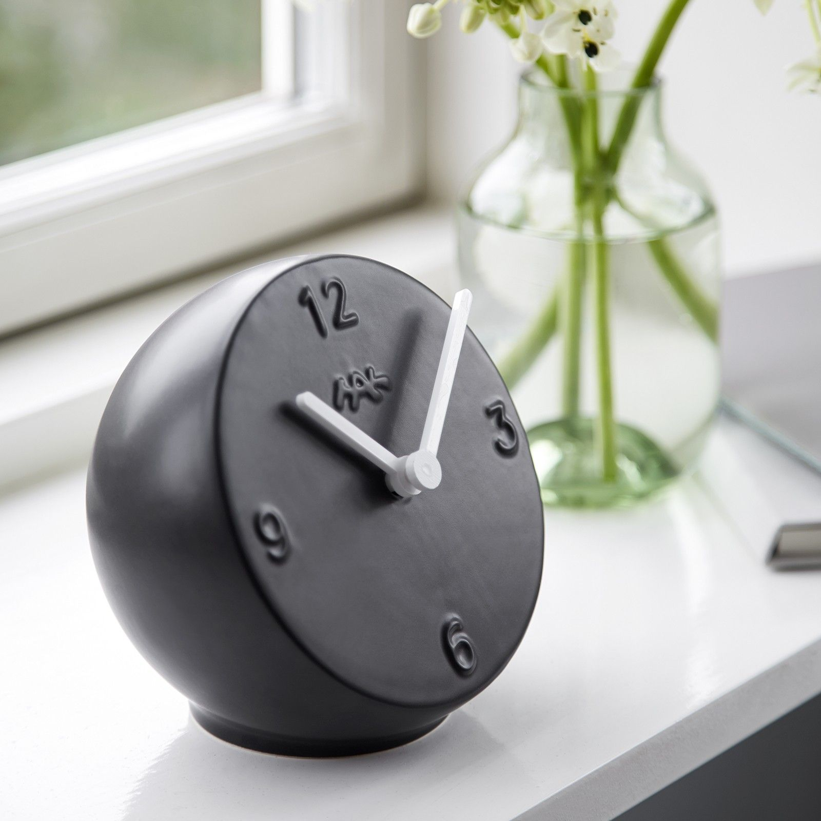 The small Ora table clock has inherited its stringent and stylish look from the popular wall clocks from Kähler in the same series, but this design gem surprises with its shape and volume.
