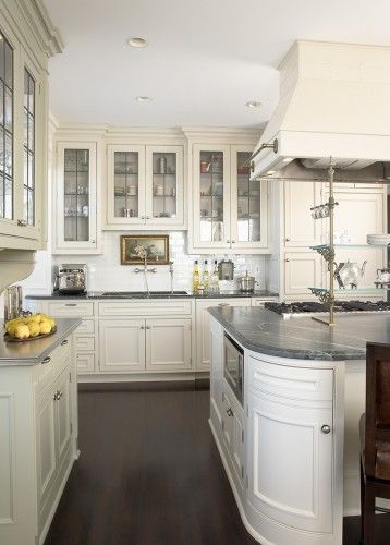 Dark stained wood floors, a mix of zinc and marble countertops and leaded glass in the cabinet doors accents a kitchen that functions as the heart of the residence  Andrew Flesher Interiors