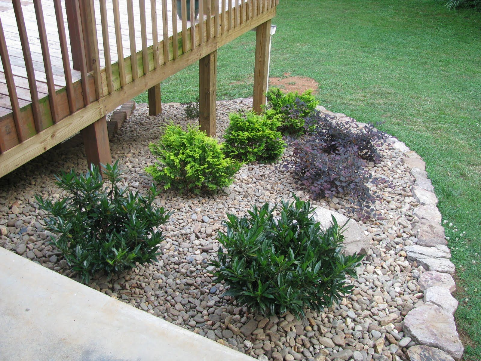 Landscaping around a deck lightsonthelake rock garden for Garden decking ideas pinterest